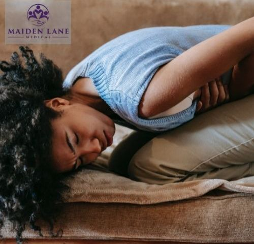 Woman experiencing endo belly pain on a couch - Endometriosis Center in NY