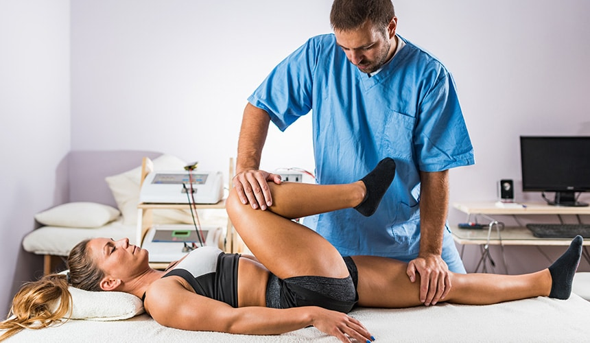 Physical therapist stretching female patient