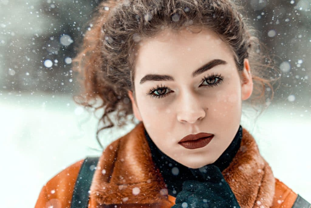 Closeup of serious woman's face with snow falling around - Skin Care Manhattan New York
