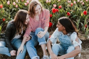3 girlfriends sitting in flower field laughing