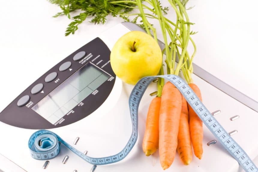 Scale and measuring tape along with an apple and carrots - Weight Loss Nutrition Manhattan New York