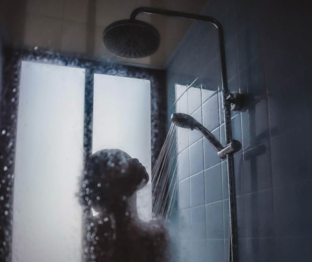Close up of Woman in shower with steamed glass