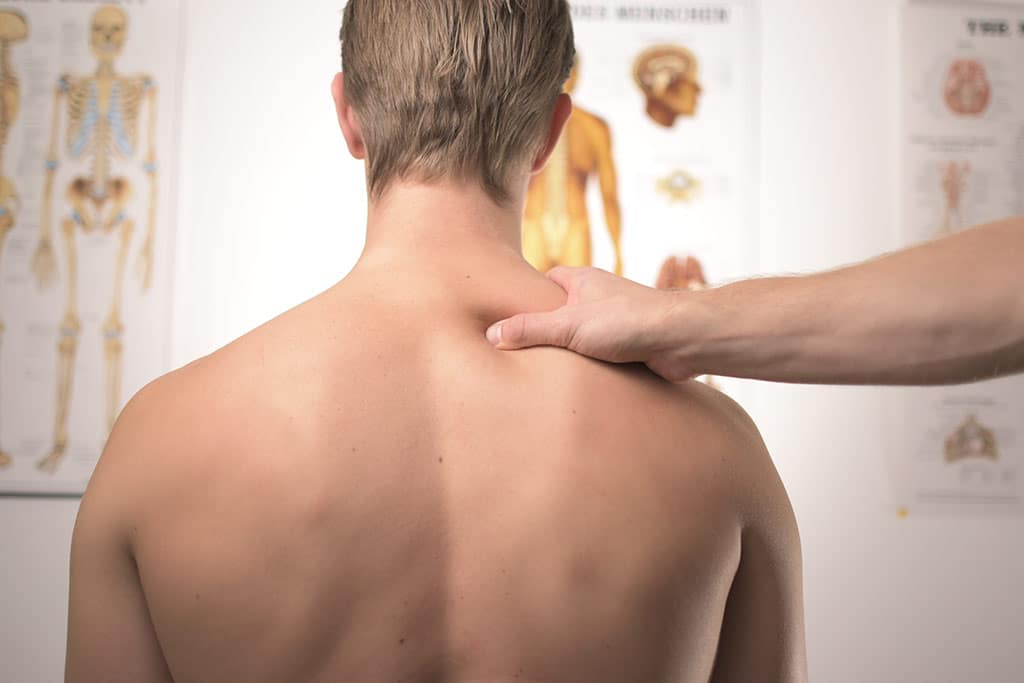 Man with bare back having shoulder probed