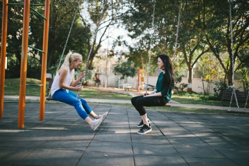 Two young women sitting on swings facing each other - Women's Health Manhattan NYC