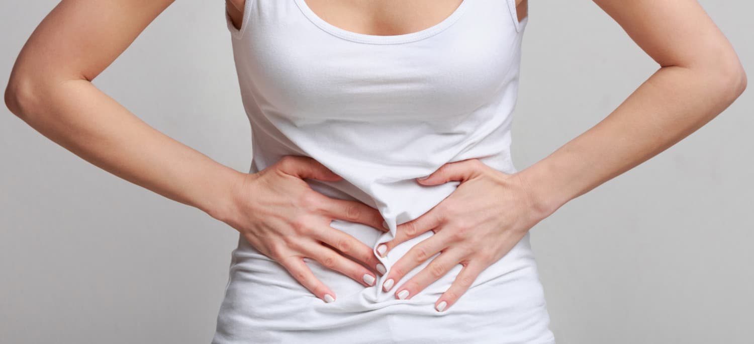 Closeup of woman with hands clutching pelvic area in pain - Pelvic Pain Manhattan New York