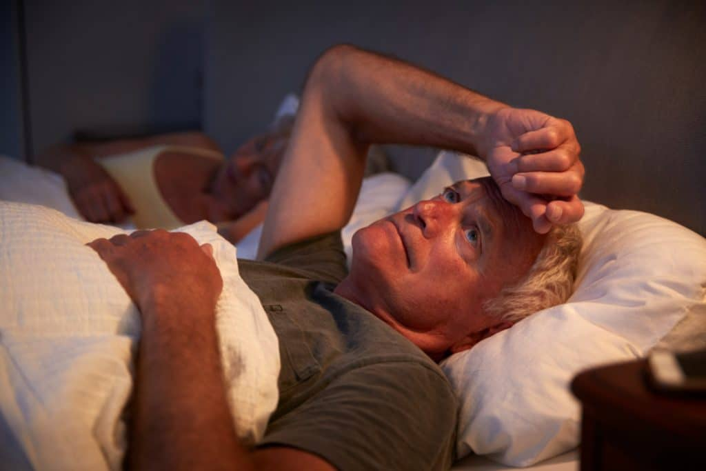 Worried senior man in bed can't sleep because of BPH - Maiden Lane Medical, NYC