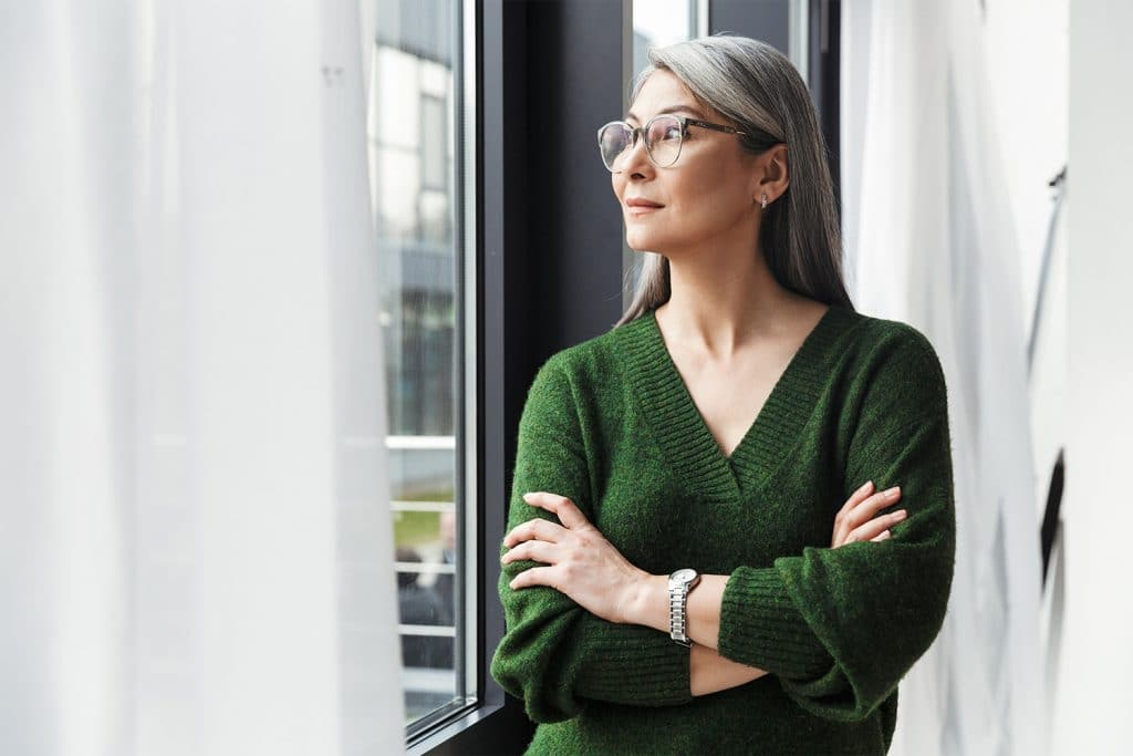 Woman wearing a green sweater thinking about UTI symptoms - Maiden Lane Medical, NYC